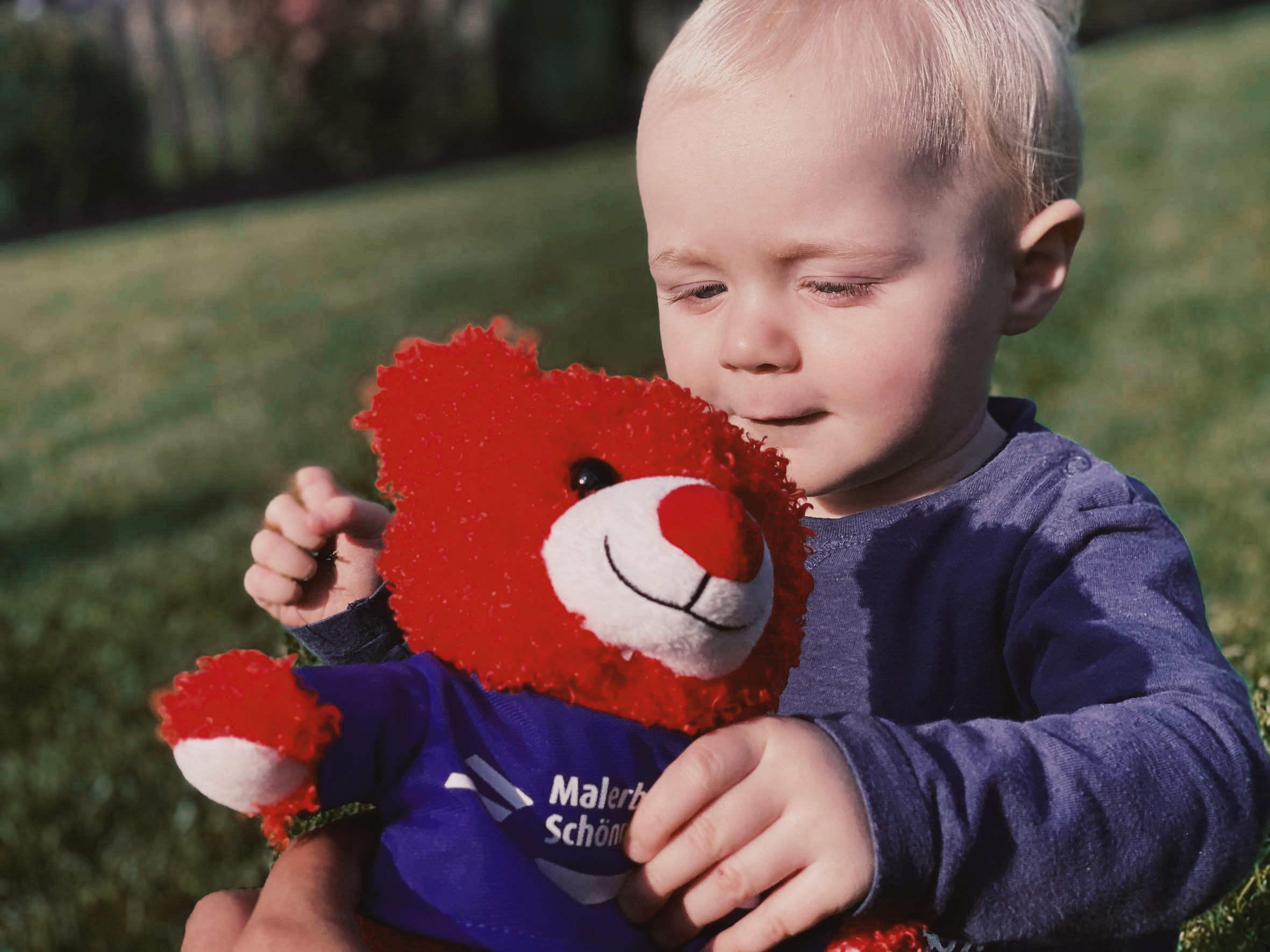 Plüsch Baby mit rotem Teddy auf dem Rasen