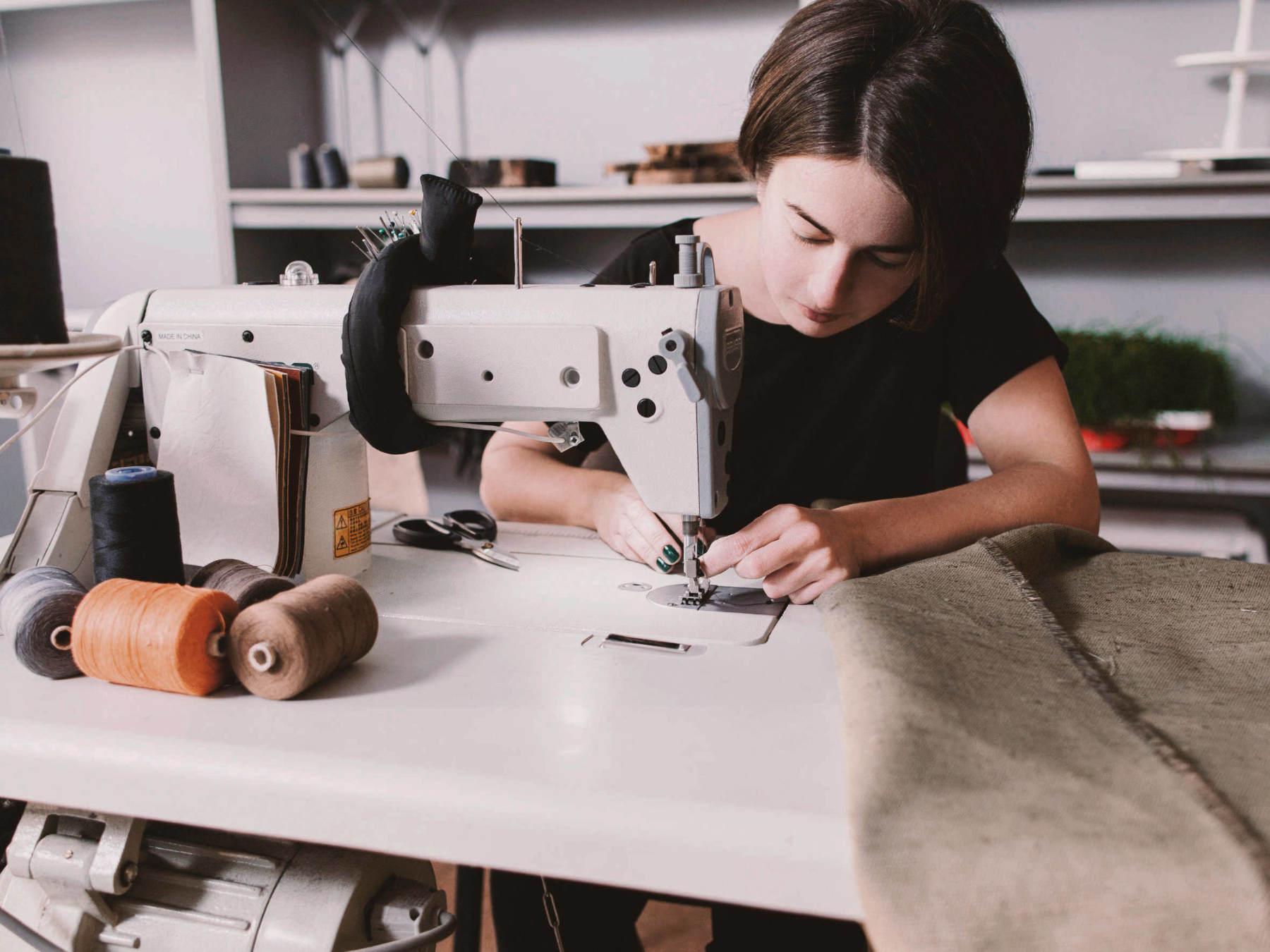 Qualität Frau sitzt an der Nähmaschine