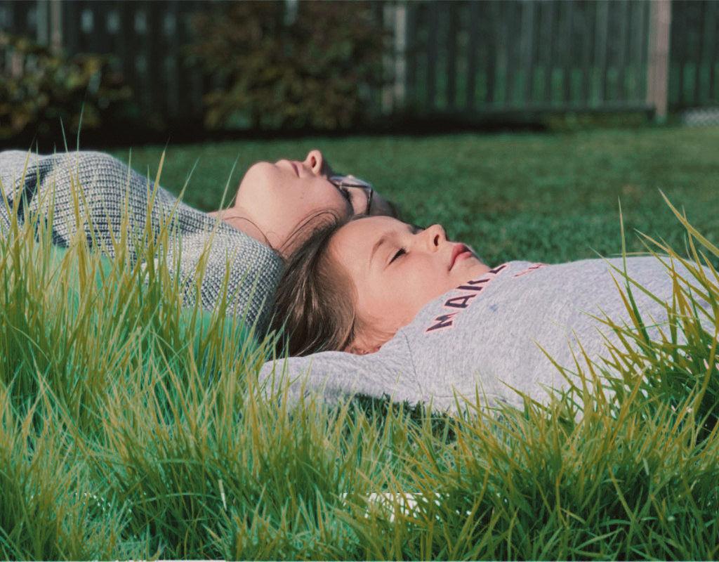 Qualität - Frau und Mädchen liegen entspannt auf der Wiese