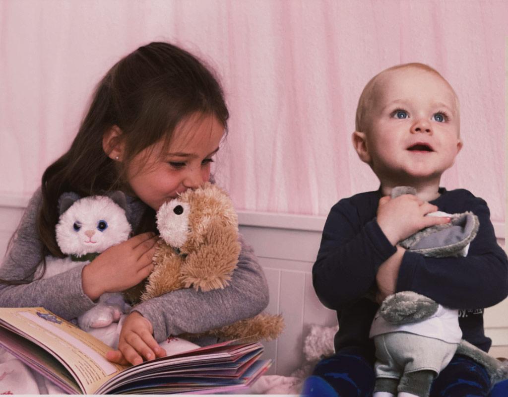 Plüschfiguren mit Kindern im Bett