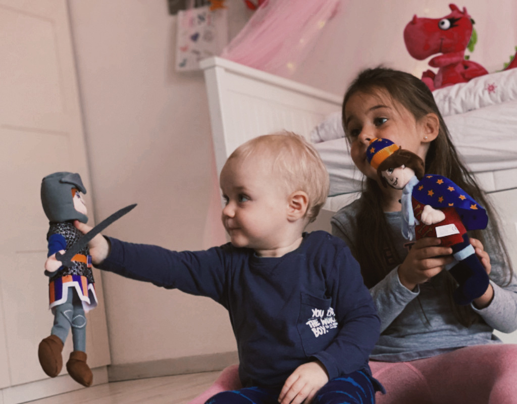 menschliche Figur Baby spielt mit Stoffpuppe
