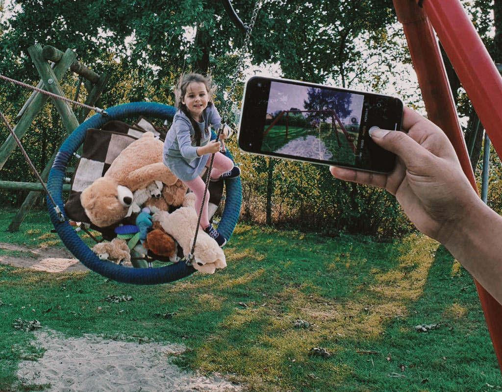 Normen Mädchen schaukelt Hand mit Handy fotografiert