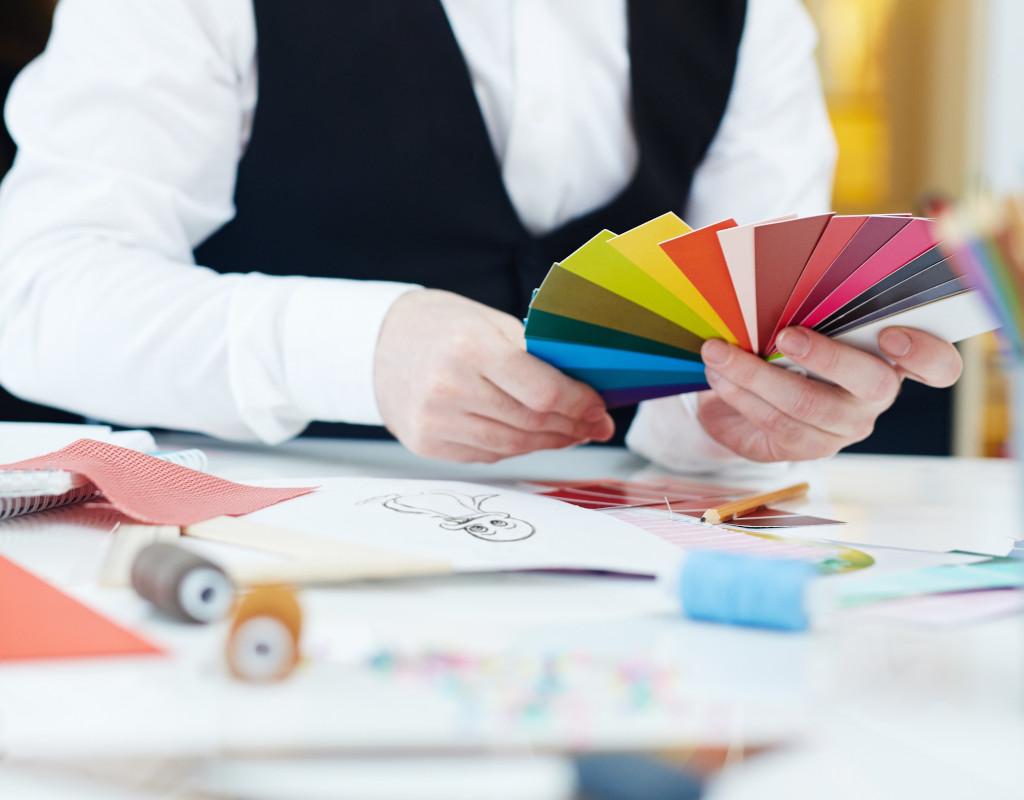 Wir Hand hält Pantonefächer Skizze und Garnrollen auf dem Tisch
