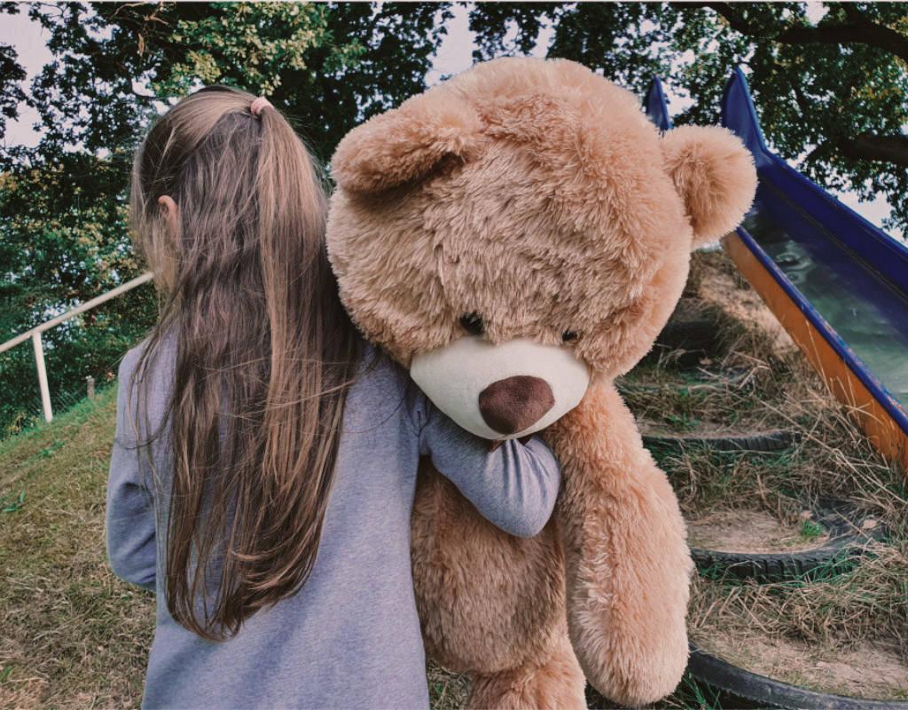 Vergleichsangebot Mädchen von hinten mit Teddy im Arm und geht Berg hinauf