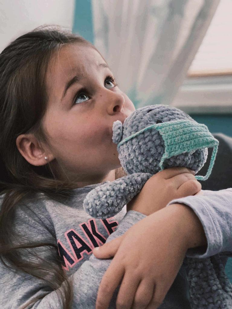 Plüsch Mädchen hält Teddy mit Maske im Arm und schaut nach oben