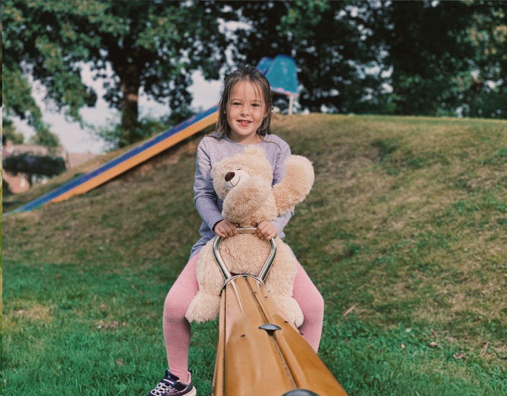Hersteller Mädchen mit Teddy auf Wippe
