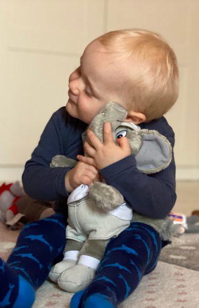 Baby kuschelt Plüschelefant auf dem Boden