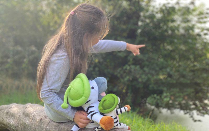 Mädchen zeigt Plüschzebras die Richtung mit dem Finger